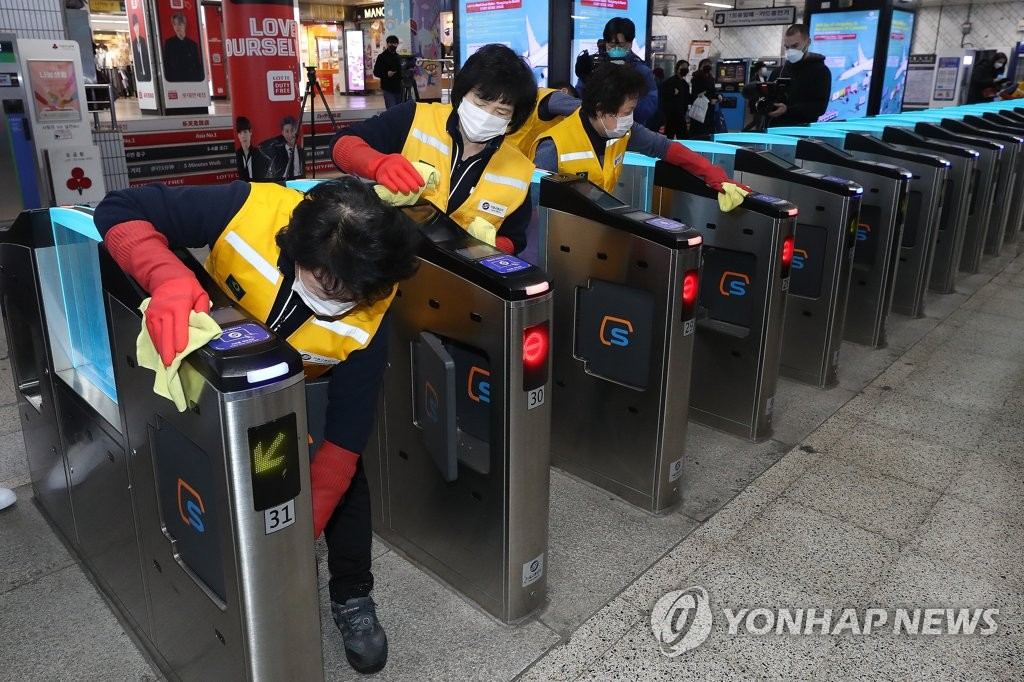 This photo, taken on March 4, 2020, shows janitors cleaning subway ticket gates at Myeongdong Station in central Seoul in a precautionary measure against the new coronavirus. The city government plans to adopt contactless gates so that passengers will not have to tag their cards at the ticket gates. (Yonhap)