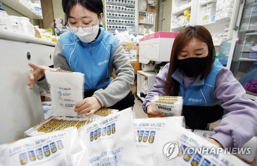 Volunteer workers package protective masks at a pharmacy in the southeastern city of Gwangju on March 23, 2020, in this photo provided by the Buk-gu district office in the city. (PHOTO NOT FOR SALE) (Yonhap)