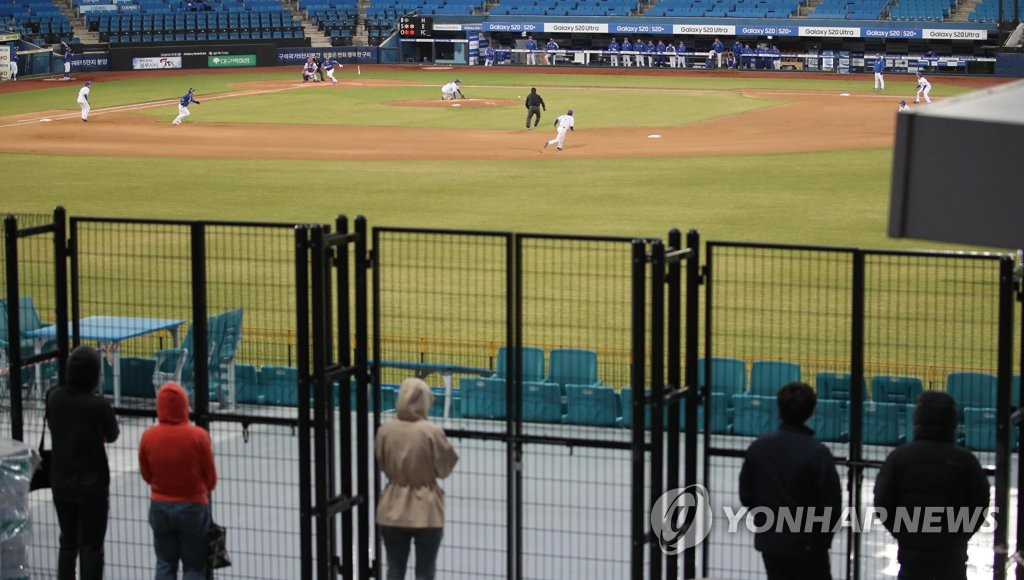 Fans watch an intrasquad game for the Samsung Lions through fences at Samsung Lions Park in Daegu, 300 kilometers southeast of Seoul, on April 16, 2020. (Yonhap)
