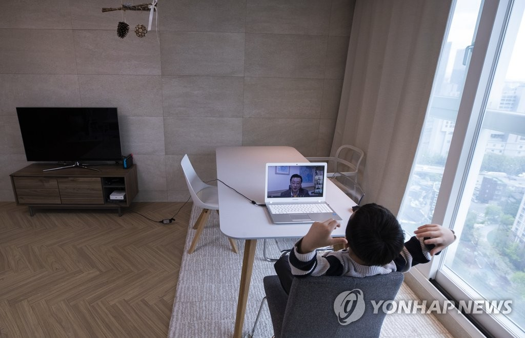 A student in the first year of elementary school takes online classes at his home in the Seoul ward of Yongsan with the help of his mother on April 20, 2020. (Yonhap)