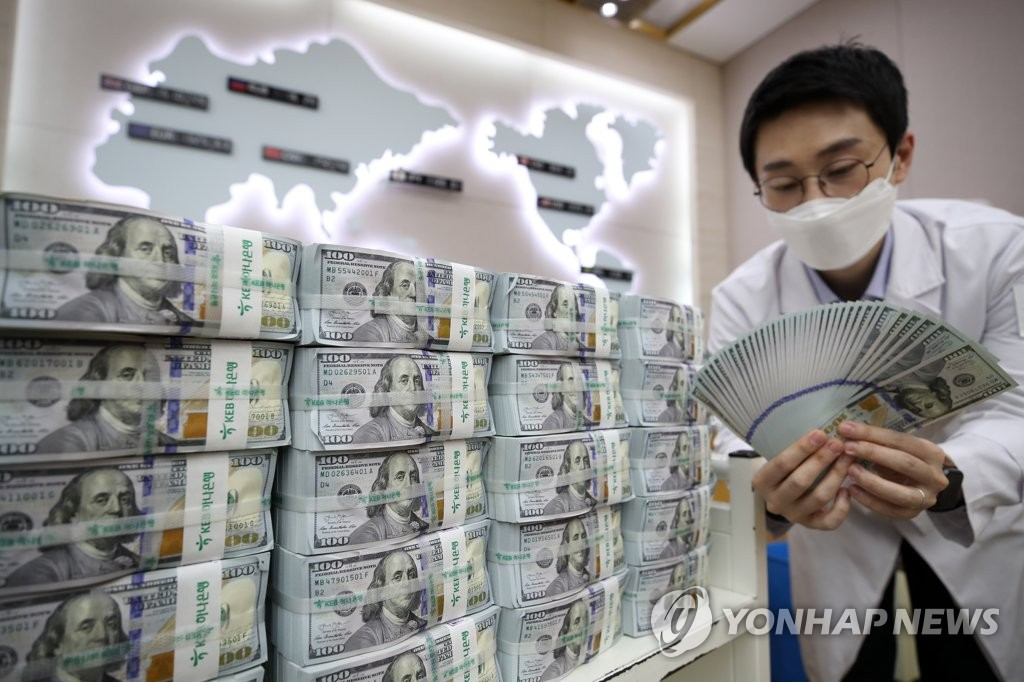 In the photo, taken April 27, 2020, a Hana Bank official inspects U.S. banknotes at a Seoul branch office. (Yonhap)