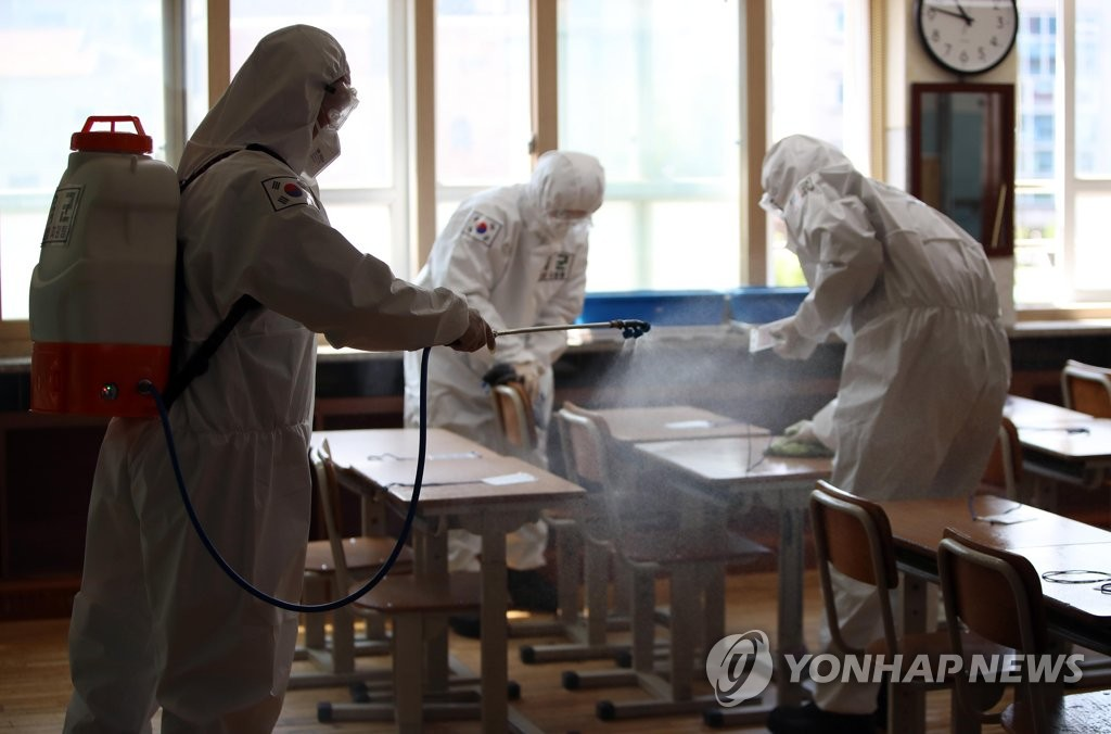 In this photo, taken on May 1, 2020, military medical soldiers disinfect a classroom at an elementary school in Daegu. (Yonhap)