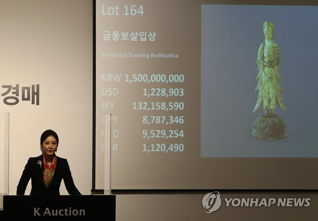 An auctioneer presents Gilt-bronze Standing Bodhisattva, which was made between the 6th and 7th centuries during the Silla period, at an auction event held at K Auction in southern Seoul on May 27, 2020. (Yonhap)