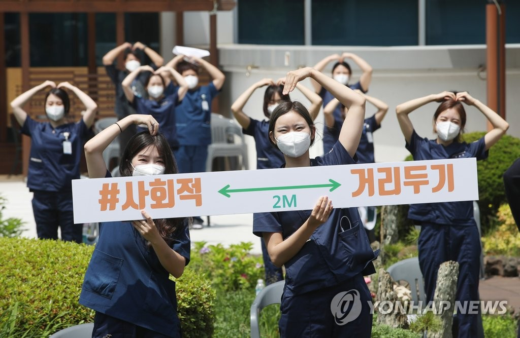Medical workers at Seoul Medical Center in northern Seoul hold a sign promoting the country's social distancing campaign on June 4, 2020. (Yonhap)