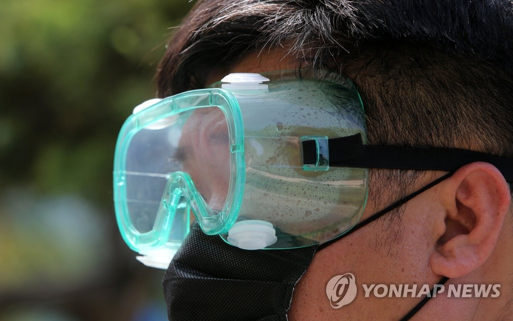 An official at the test venue of an exam for public servants in Chuncheon, east of Seoul, sweats in the summer heat on June 13, 2020. (Yonhap)