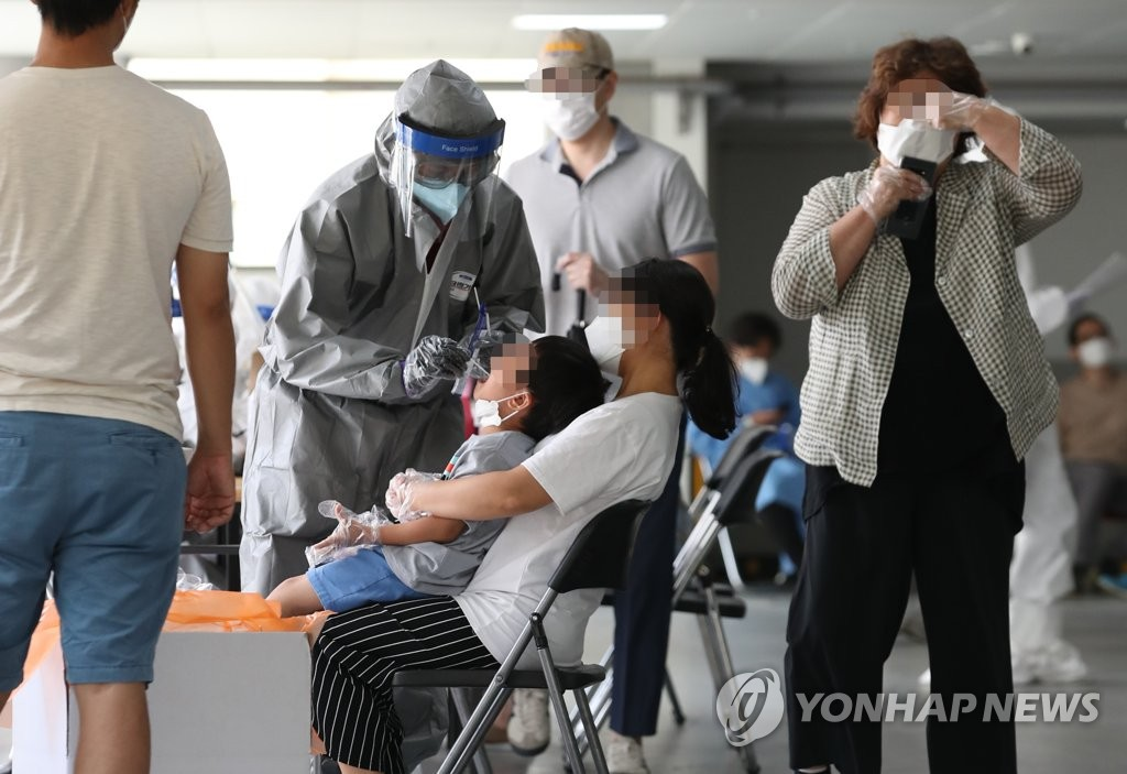 Seoul citizens go through new coronavirus tests at a temporary testing site established at Wangsung Church in the southeastern area of the capital on June 26, 2020. (Yonhap)
