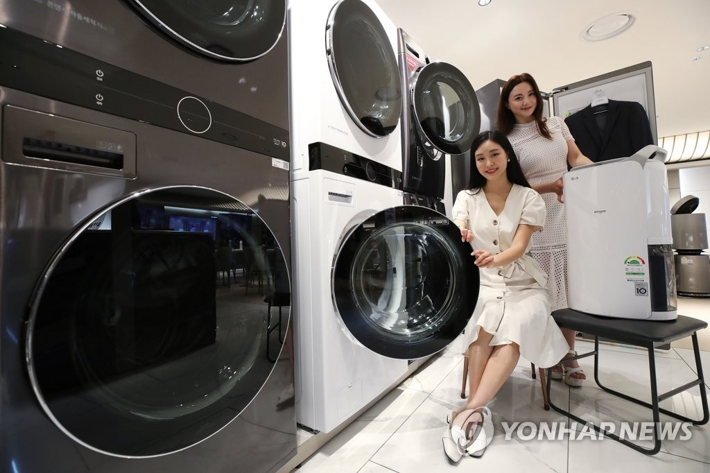 This file photo taken June 29, 2020, shows models promoting LG Electronics Inc.'s home appliance products at a store in Seoul. (Yonhap)