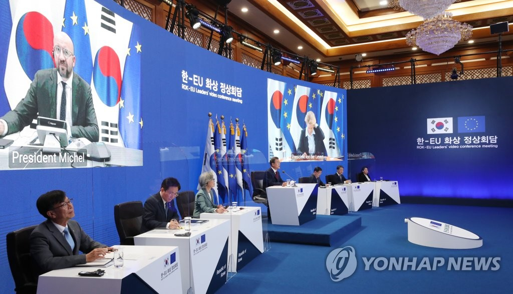 South Korean President Moon Jae-in (C) holds a videoconference meeting with EU Council President Charles Michel and European Commission President Ursula von der Leyen at Cheong Wa Dae in Seoul on June 30, 2020, with the EU leaders appearing on large screens. (Yonhap)