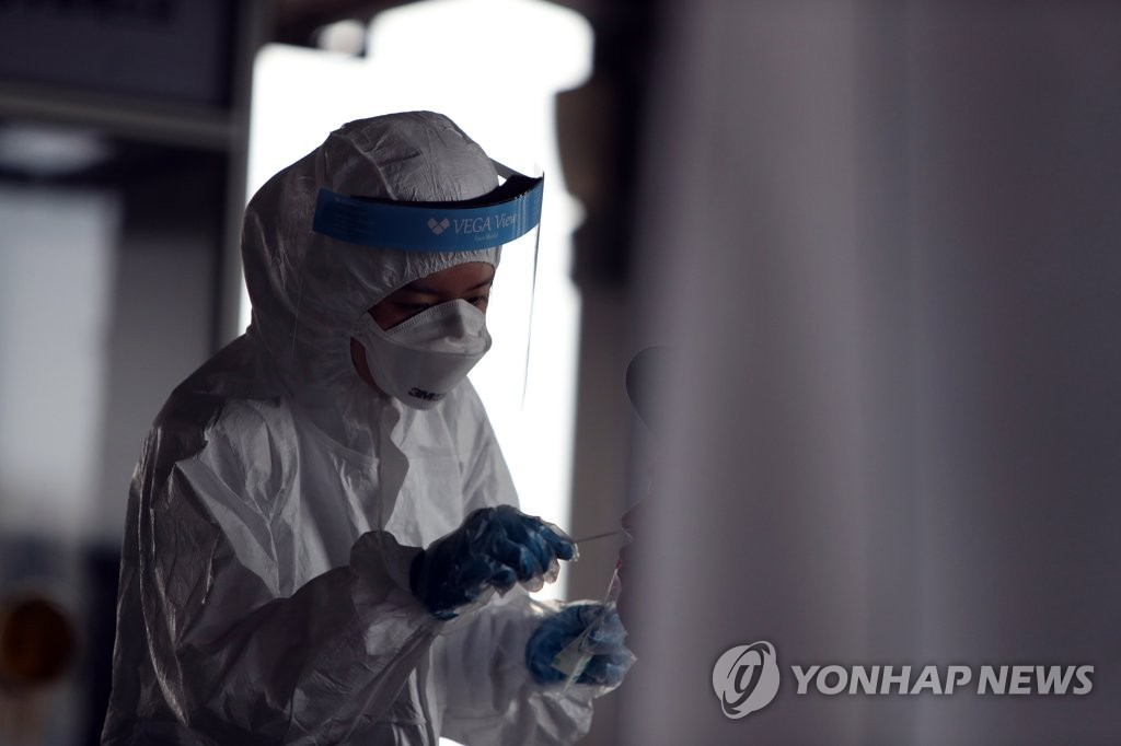 A medical worker carries out new coronavirus tests at an elementary school in Daejeon, 164 kilometers south of Seoul, on July 2, 2020. (Yonhap)