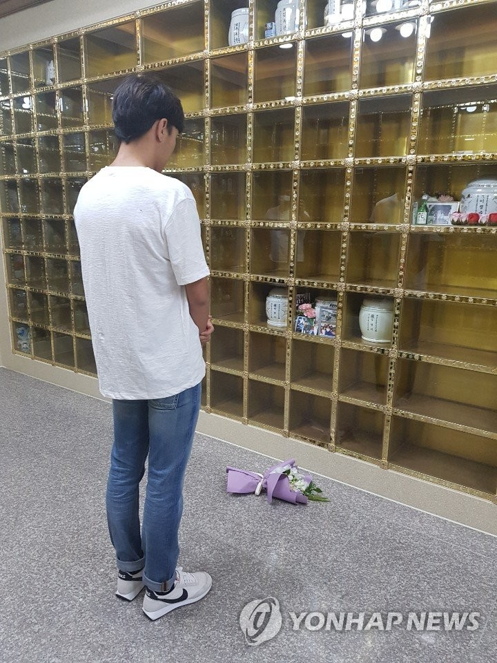 In this photo, provided by a reader on July 9, 2020, triathlete Kim Do-hwan stands before an urn containing remains of his late teammate Choi Suk-hyeon to pay his respects at a memorial park in Seongju, 300 kilometers southeast of Seoul. Kim admitted to allegations made earlier by Choi that he had physically assaulted her while they were teammates for Gyeonggju City Hall club. (PHOTO NOT FOR SALE) (Yonhap)