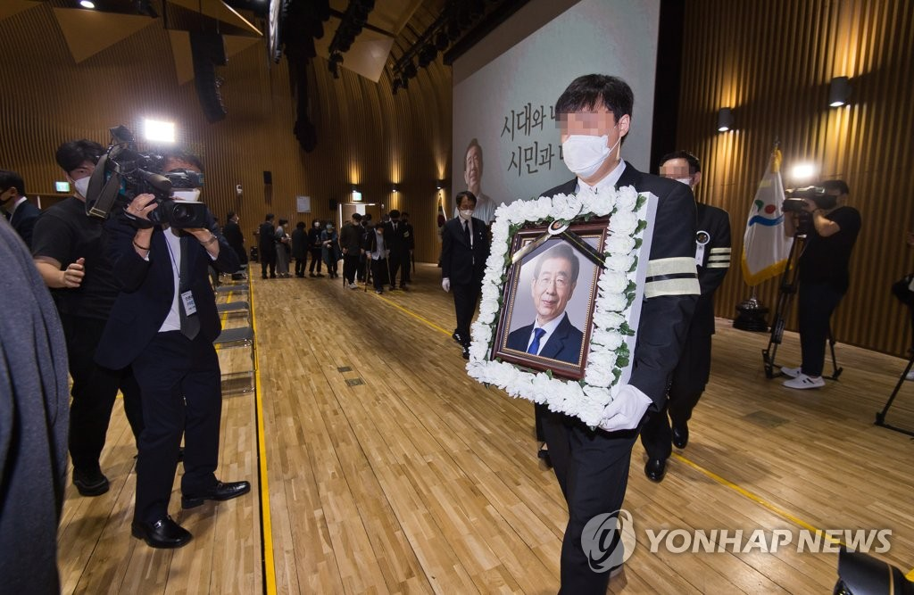 A photo of late Seoul Mayor Park Won-soon is carried outside of City Hall in central Seoul following a livestreamed funeral service on July 13, 2020. (Yonhap)