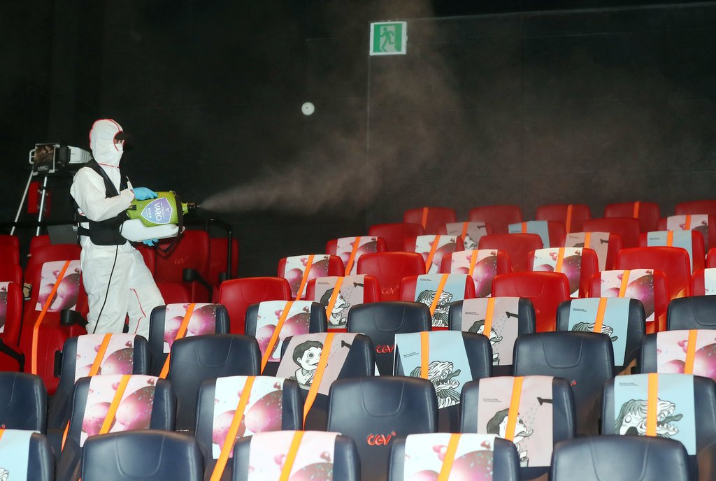 This file photo taken on July 14, 2020, shows a worker disinfecting a CGV theater in Bucheon, just west of Seoul, to prevent spread of the new coronavirus. (Yonhap)