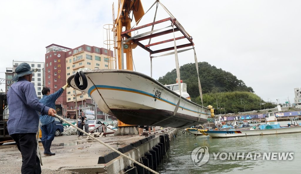 This photo, from Aug. 9, 2020, shows fishermen in the southeastern port city of Busan moving ships to dry land to prepare for Typhoon Jangmi, which was expected to hit South Korea this week. (Yonhap)