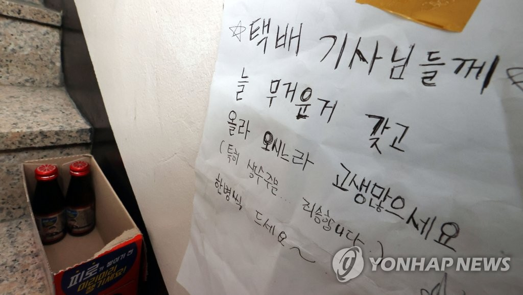 A handwritten thank-you note is posted at a residential building in Seoul, along with vitamin drinks, on Aug. 13, 2020, a day before the industry went on a one-day special holiday. (Yonhap)