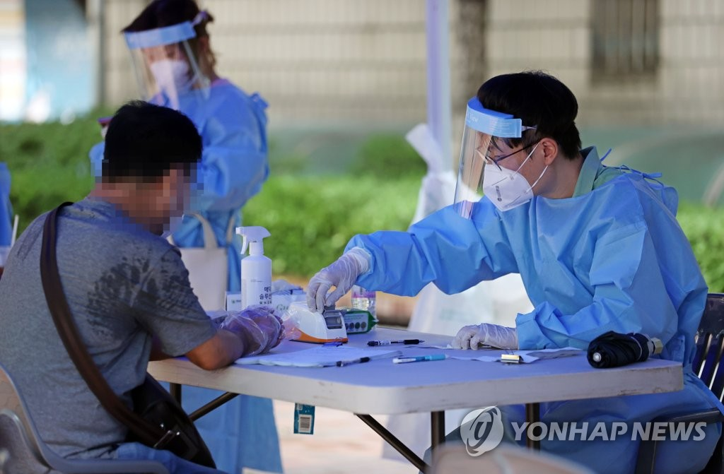 A health worker at a screening center set up in the central Seoul ward of Jung assists a visitor on Aug. 14, 2020. (Yonhap)