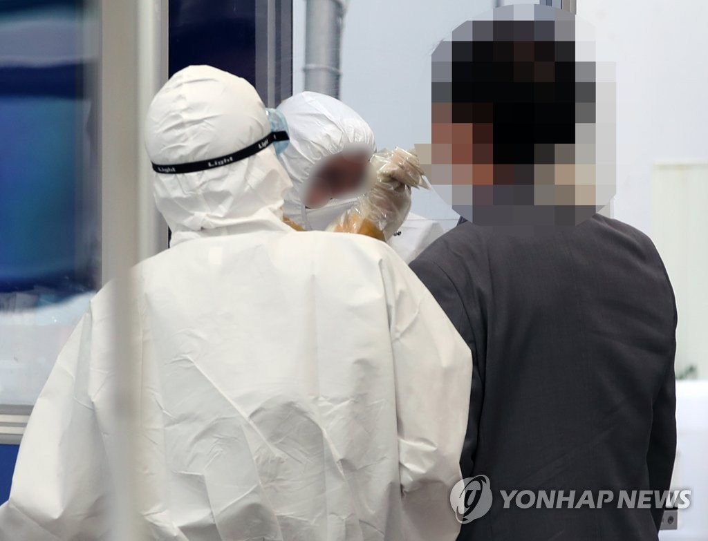 Health workers clad in protective gear conduct a COVID-19 test on a citizen at a virus screening clinic in Seoul on Sept. 17, 2020. (Yonhap)
