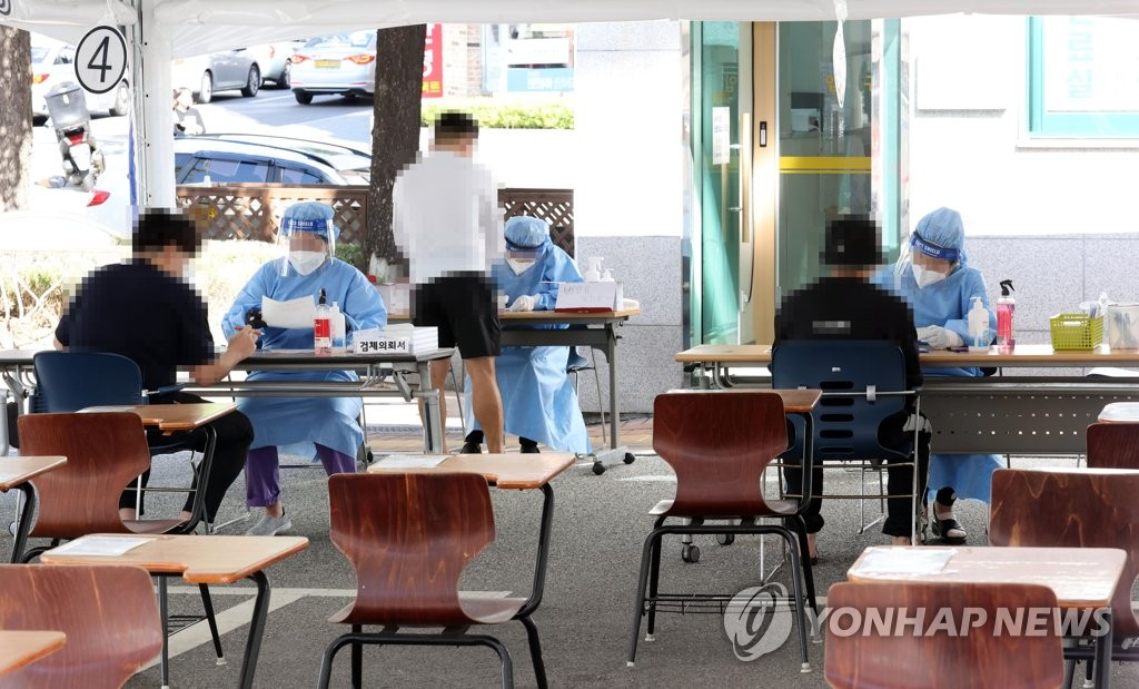 Health workers clad in protective gear guide citizens at a virus screening clinic in Seoul on Sept. 24, 2020. (Yonhap)