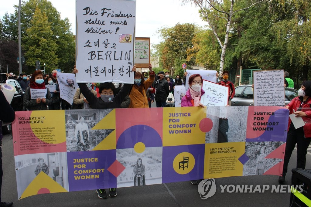 Activists and citizens march in protest of the Mitte district office's order to remove a statue symbolizing victims of Japan's wartime sexual slavery in Berlin on Oct. 13, 2020. (Yonhap)