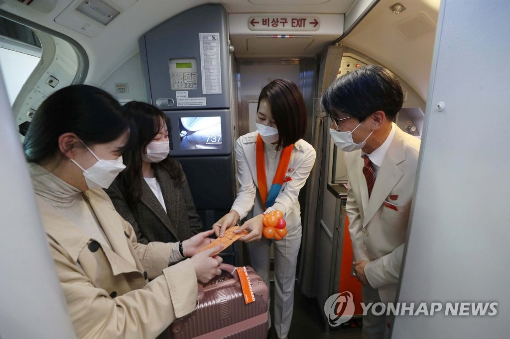 This photo, provided by the Incheon International Airport press pool, shows flight crew checking boarding passes on a Jeju Air flight to nowhere on Oct. 23, 2020. (Yonhap)