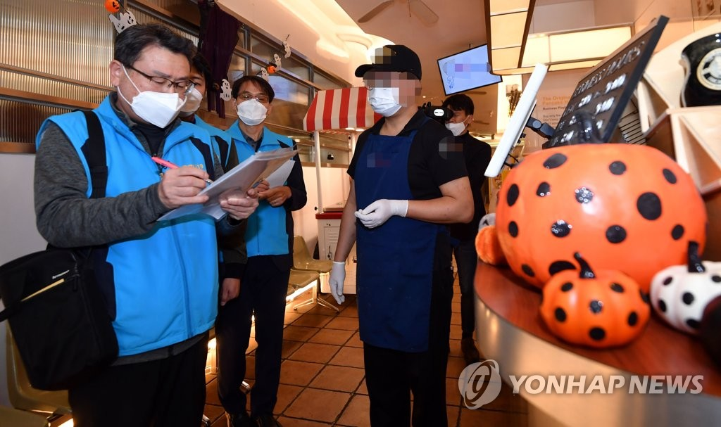 In the file photo taken Oct. 29, 2020, Seoul city officials monitor a visitor check-in system at a restaurant in Itaewon in Seoul ahead of Halloween on concerns over the spread of COVID-19. (Yonhap)