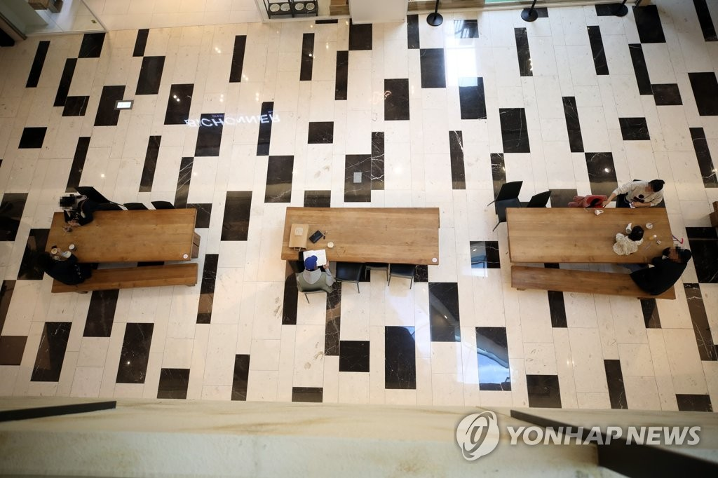 Visitors sit at tables while keeping a safe distance at a shopping mall in Seoul on Nov. 8, 2020. (Yonhap)