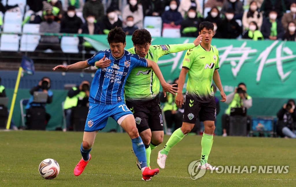Kim Bo-kyung of Jeonbuk Hyundai Motors (C) and Lee Chung-yong of Ulsan Hyundai FC battle for the ball during the second leg of the FA Cup final at Jeonju World Cup Stadium in Jeonju, 240 kilometers south of Seoul, on Nov. 8, 2020. (Yonhap)