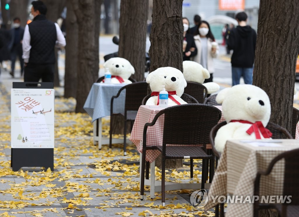 Teddy bears sit on one side of tables with hand sanitizer on a sidewalk in downtown Seoul on Nov. 17, 2020, to pair with people who want to take a break while keeping at a distance from others. (Yonhap)