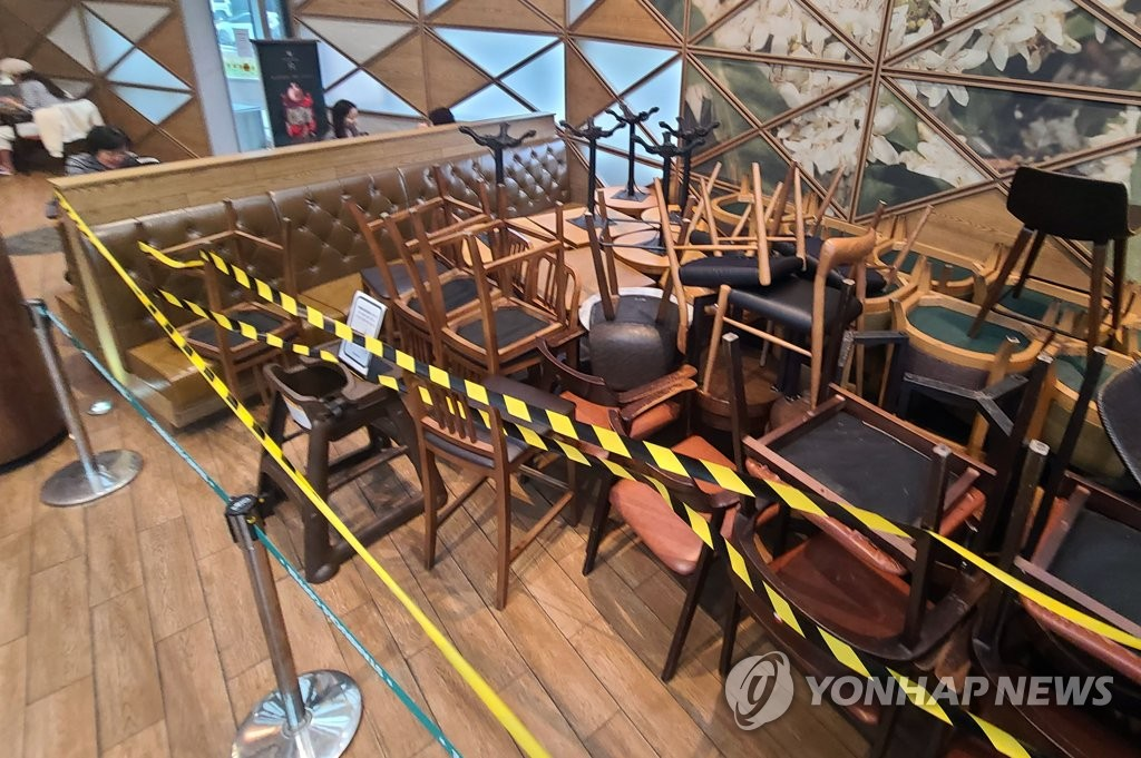Tables and chairs are piled up at a coffee shop in Seoul on Nov. 18, 2020, a day before tightened social distancing goes into effect. (Yonhap)