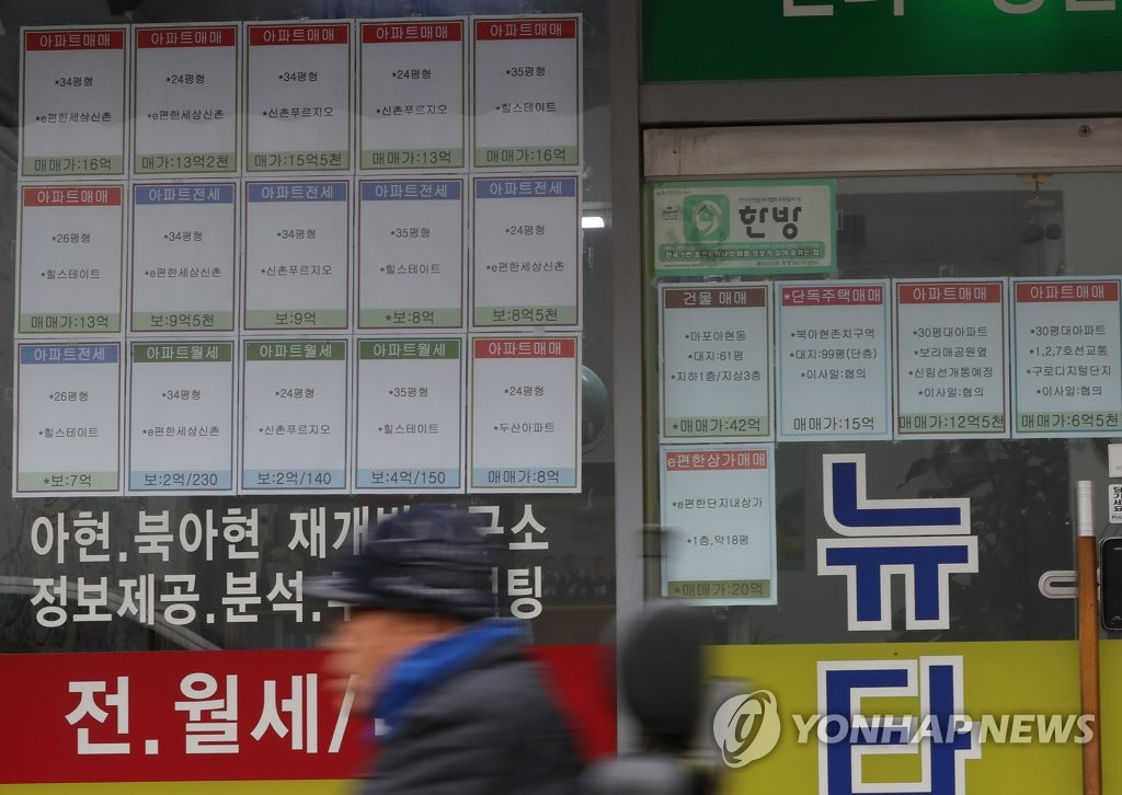 A pedestrian passes by a real estate brokerage office in western Seoul on Nov. 2020. (Yonhap)