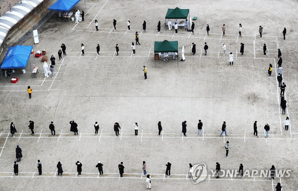 Students and teachers wait in line to receive COVID-19 tests at a high school in Sejong on Nov. 27, 2020, after one student tested positive for COVID-19. (Yonhap)