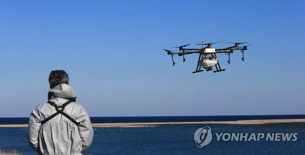 An official controls a drone to spray disinfectant at a seasonal home for migratory birds in Yangyang, 215 kilometers east of Seoul, on Nov. 29, 2020. (Yonhap)