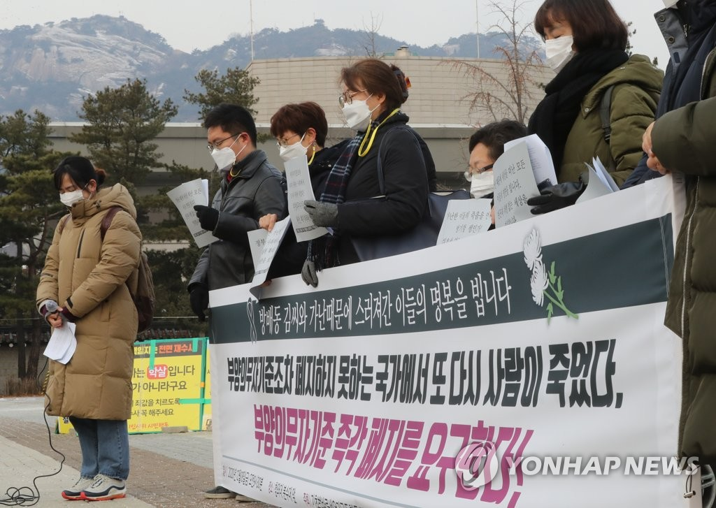 In this file photo taken Dec. 18, 2020, civic group activists offer a silent tribute to a mother who died after struggling with economic hardships, leaving behind a mentally impaired son, in front of Cheong Wa Dae in Seoul. (Yonhap)