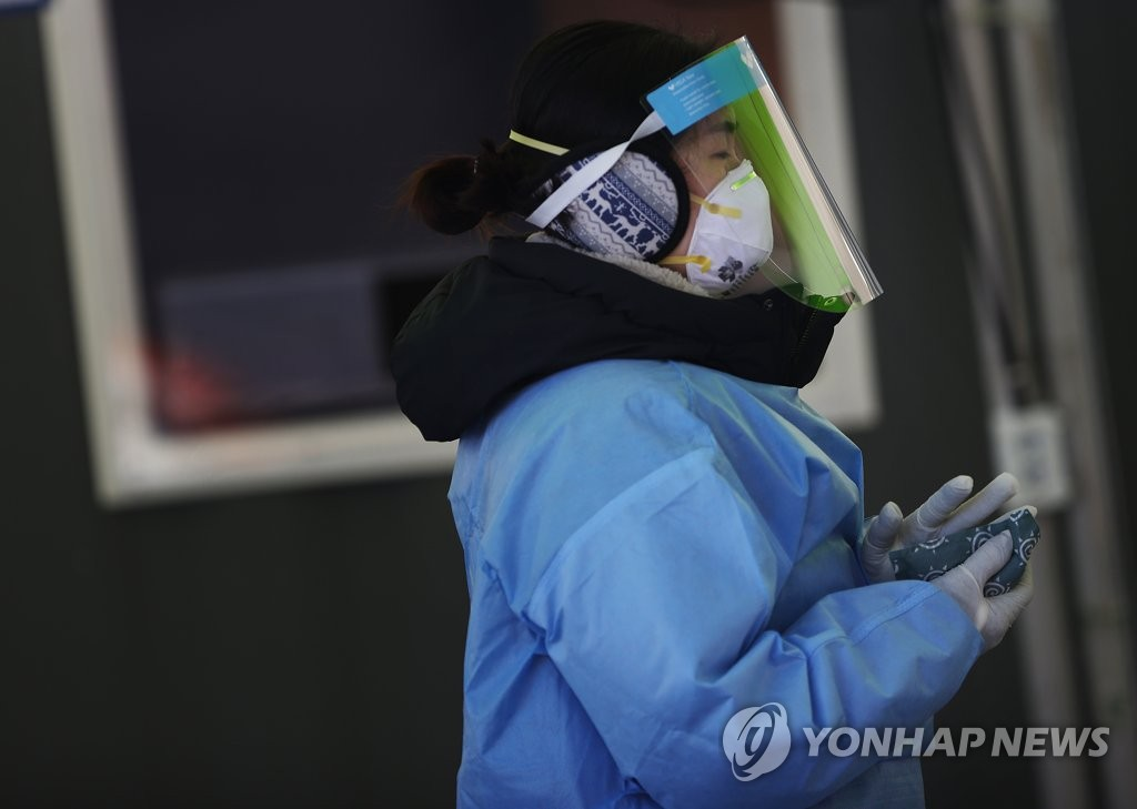 A medical worker warms her hands with instant hot packs at a makeshift clinic for coronavirus testing in front of Seoul Station on Jan. 10, 2021, amid a cold wave sweeping the country. (Yonhap)
