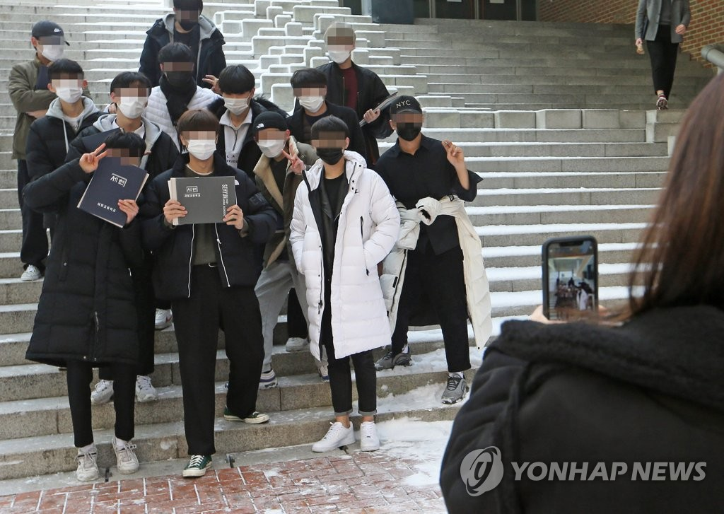 High school students wearing protective masks pose for a photo during a graduation ceremony on Jan. 13, 2021. (Pool photo) (Yonhap)