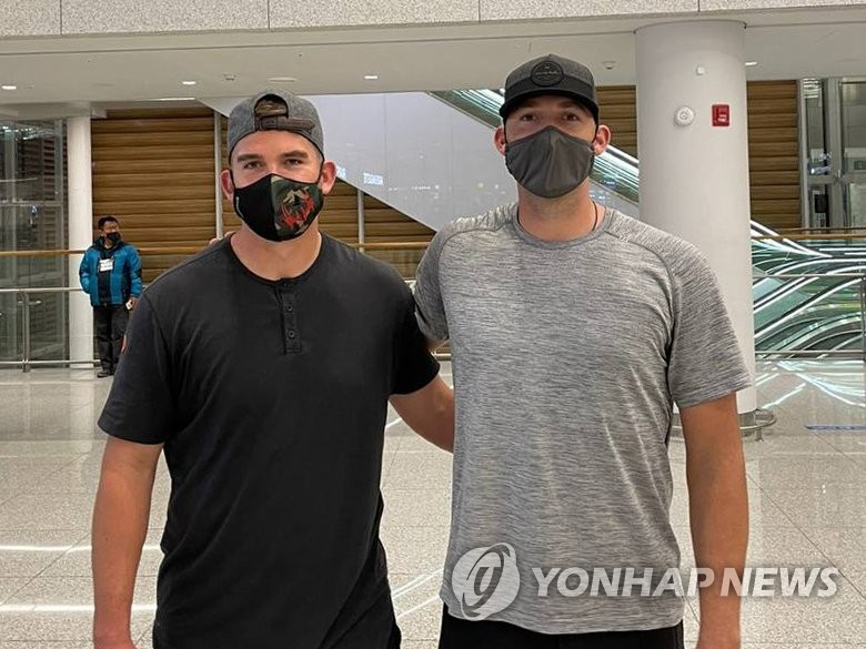 Ryon Healy (L) and Ryan Carpenter of the Hanwha Eagles pose for photos after landing at Incheon International Airport in Incheon, west of Seoul, on Jan. 17, 2021, in this photo provided by the Eagles. (PHOTO NOT FOR SALE) (Yonhap)