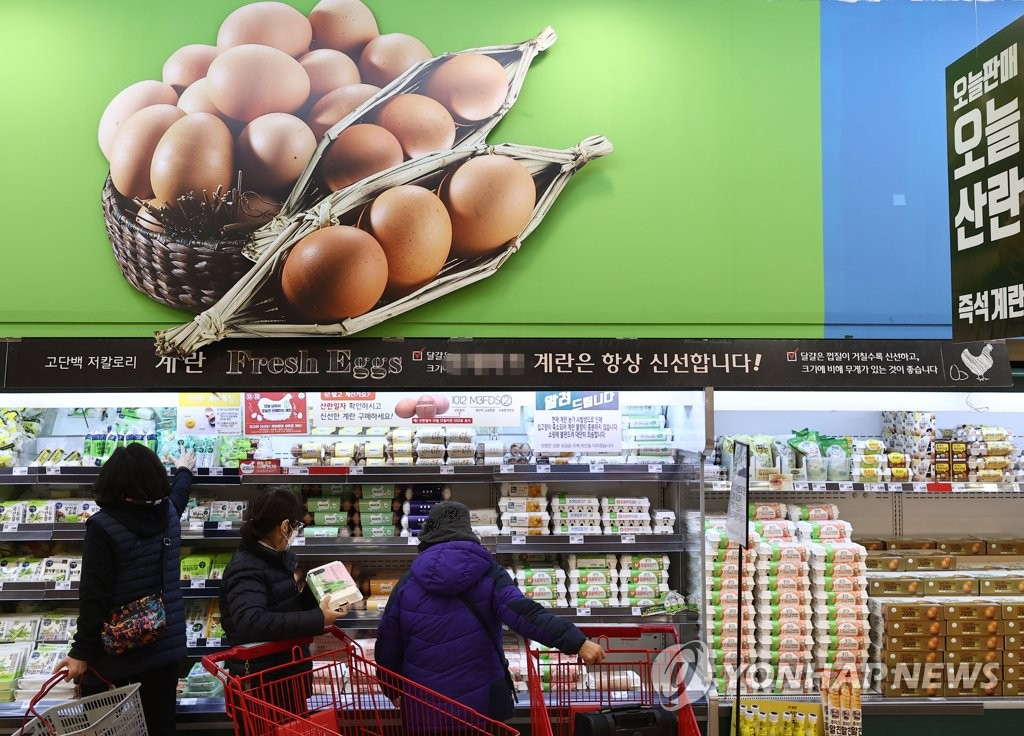 Shoppers pick eggs at a supermarket in Seoul on Jan. 20, 2021. (Yonhap)