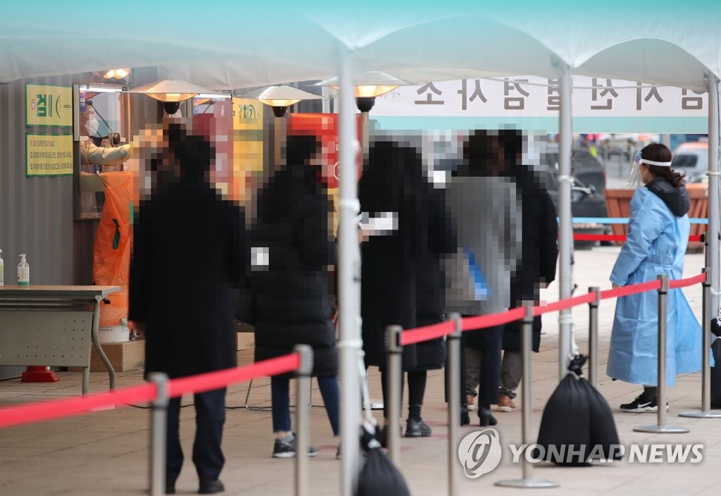 Citizens wait in line to receive virus tests at a makeshift virus testing clinic in Seoul on Jan. 21, 2021. (Yonhap)
