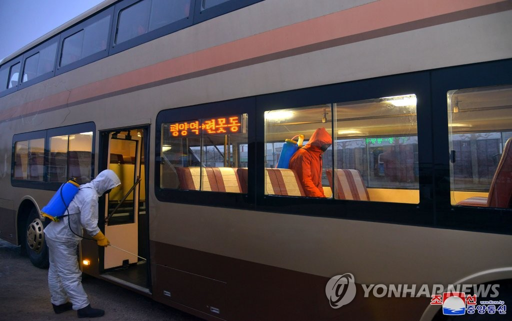 Officials disinfect a bus in Pyongyang amid the coronavirus pandemic, in this undated photo released by the North's official Korean Central News Agency on Feb. 19, 2021. North Korea has claimed to be coronavirus-free, but it has implemented relatively swift and extensive antivirus efforts since early last year, including border controls restricting movement of people and goods between the North and China. (For Use Only in the Republic of Korea. No Redistribution) (Yonhap)