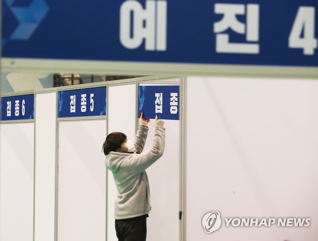 A worker puts up signs at a makeshift COVID-19 vaccination center in Suwon, 46 kilometers south of Seoul, on Feb. 22, 2021. (Yonhap)
