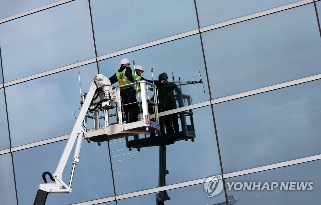 Workers clean the exterior glass wall of the Incheon International Airport's No. 2 Terminal in Incheon, west of Seoul, on March 25, 2021. (Yonhap)