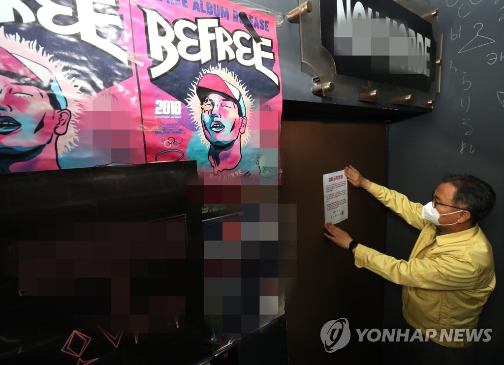 An official of the southern port city of Busan attaches a sign on a ban on the front door of a bar on April 12, 2021, amid a virus resurgence. (Yonhap)