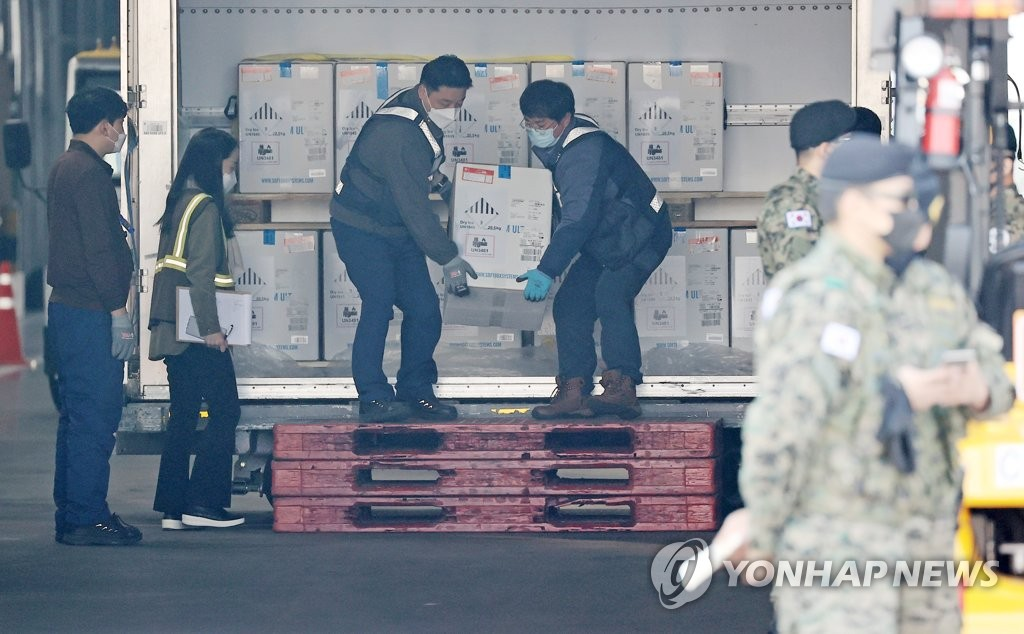 Workers unload Pfizer Inc.'s COVID-19 vaccine from a cargo plane at Incheon International Airport, west of Seoul, on April 21, 2021. (Yonhap)