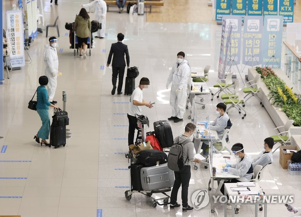 Quarantine officials guide foreigners who arrived at Incheon International Airport, west of Seoul, on May 5, 2021. (Yonhap)