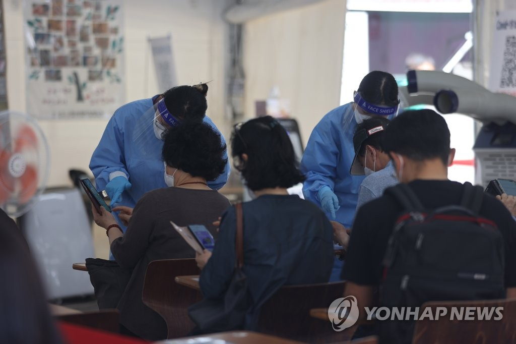 Medical workers explain the testing process to those waiting in line at a COVID-19 test center in southern Seoul on May 19, 2021. (Yonhap)