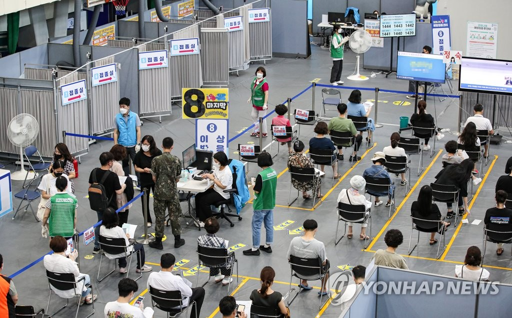 People wait in line to receive COVID-19 vaccines at an inoculation center in southern Seoul on Aug. 6, 2021. (Yonhap)
