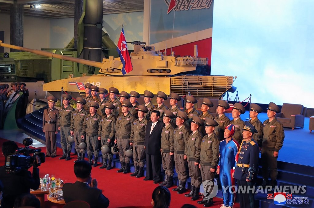 North Korean leader Kim Jong-un (7th from R, front row) poses during a visit to a defense development exhibition, Self-Defence-2021, in Pyongyang on Oct. 11, 2021, in this photo released by the Korean Central News Agency. (For Use Only in the Republic of Korea. No Redistribution) (Yonhap)